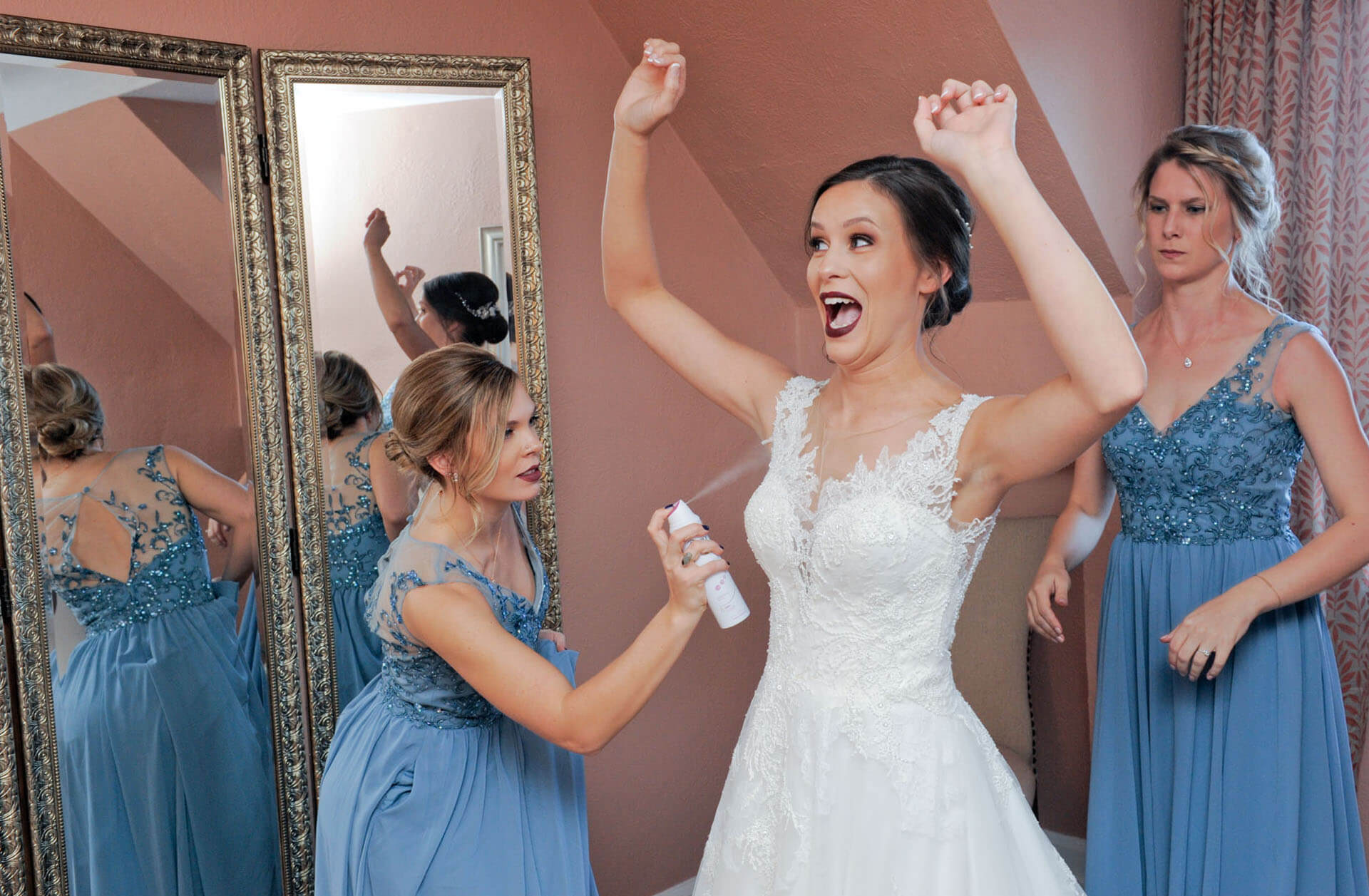 Photojournalist wedding moments at their best in Detroit, Michigan as a bride reacts to getting sprayed with chilly deodorant before her wedding.