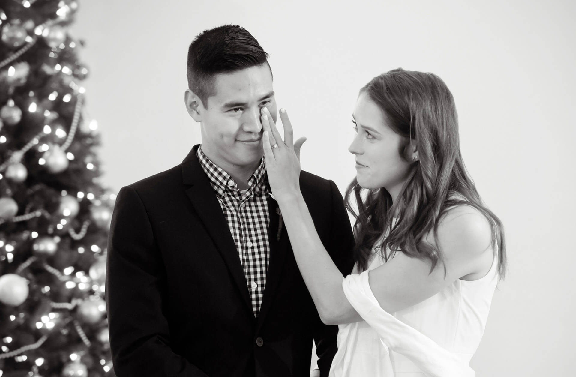 The bride wipes a tear away from the groom's eye during their intimate Troy, Michigan wedding.