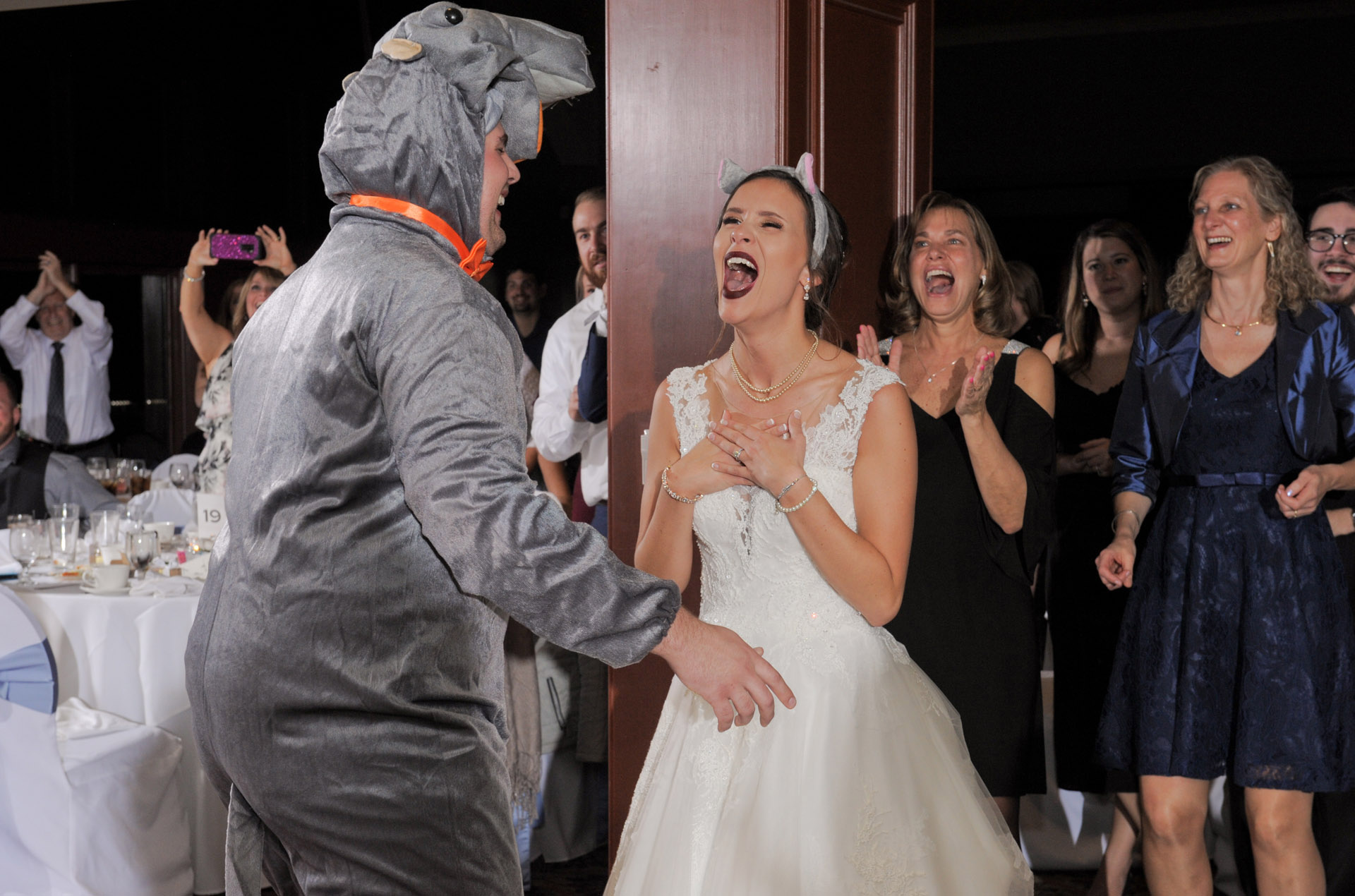 The bride squeals with delight when the groom showed up to their first dance in a hippo outfit during their Detroit, Michigan.