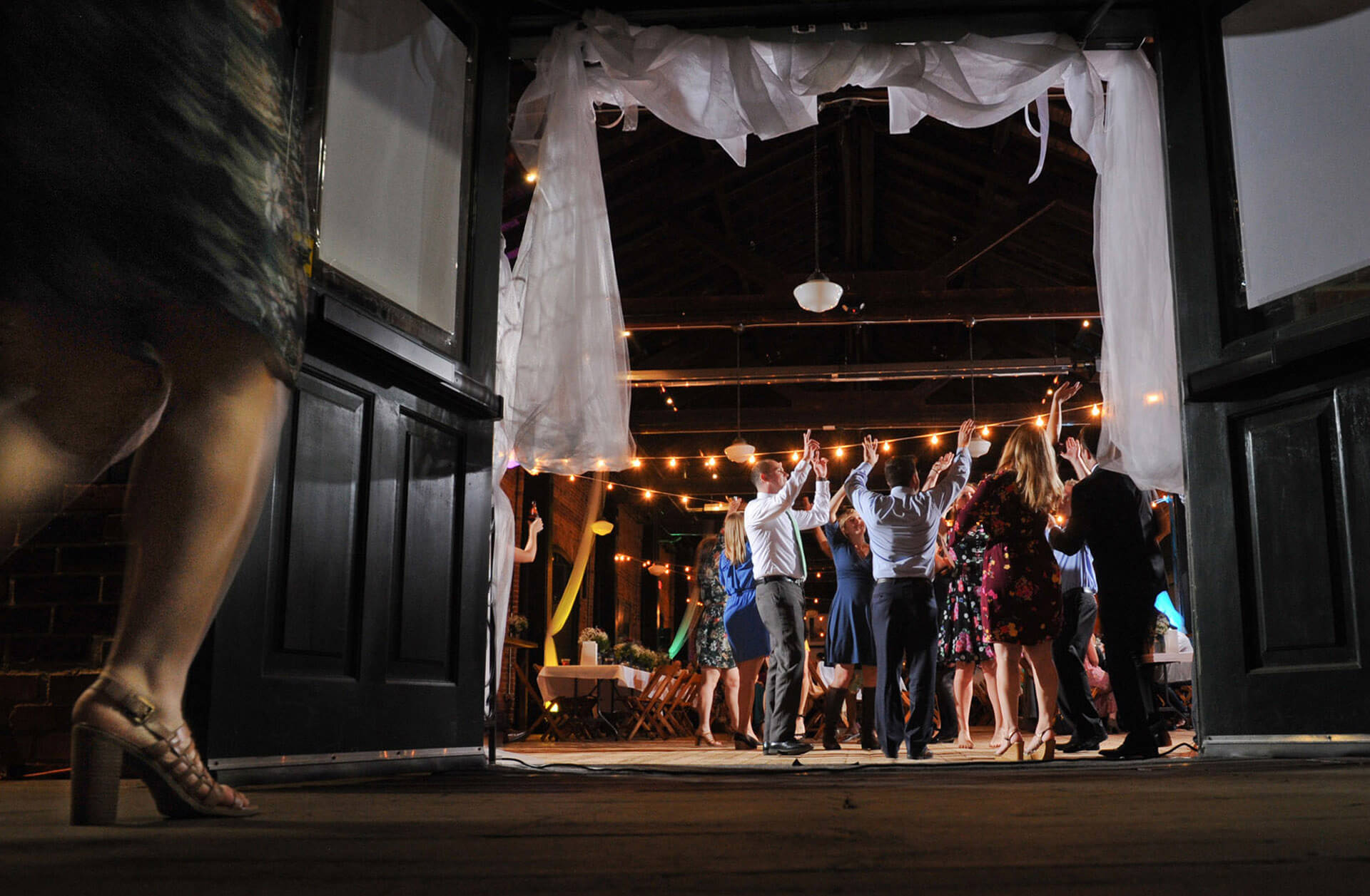 A wedding guest runs back into the Freighthouse to dance to a song during the wedding reception in Ypsilanti, Michigan.
