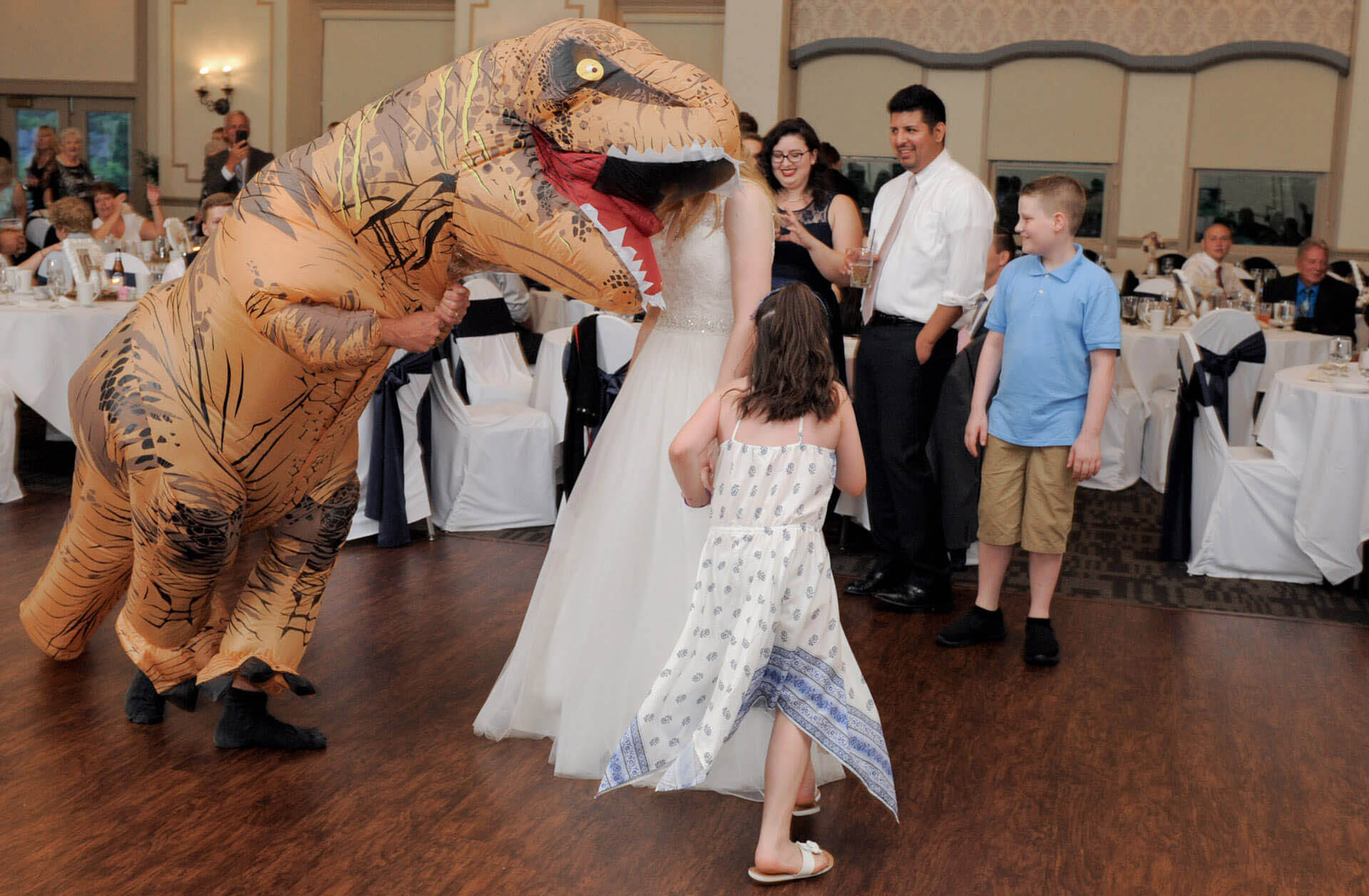 A fun, goofy photo of a bride that seems to be having her head chewed during her Polo Fields, Ann Arbor Michigan wedding is purely an optical illusion during the dancing portion of the wedding reception.