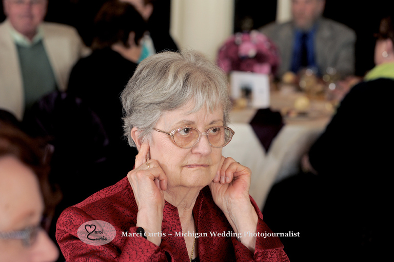 Grandmother covers her ears as the volume in the room of the wedding reception increases.