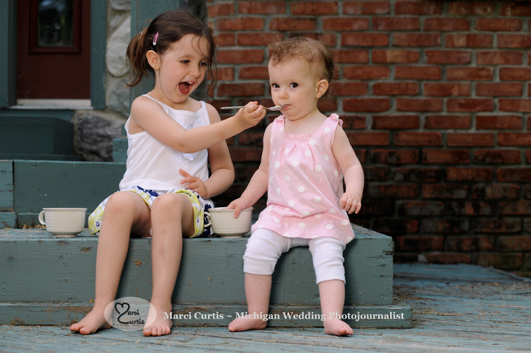Big sister feeds her baby sister ice cream during Michigan family photo shoot.