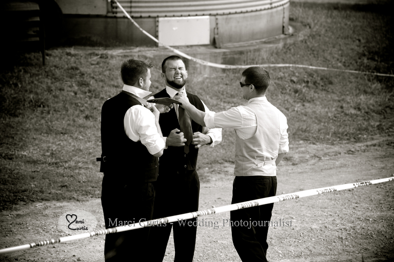 The groom adjusts his groomsmen's ties before his country wedding on his family farm in Michigan.