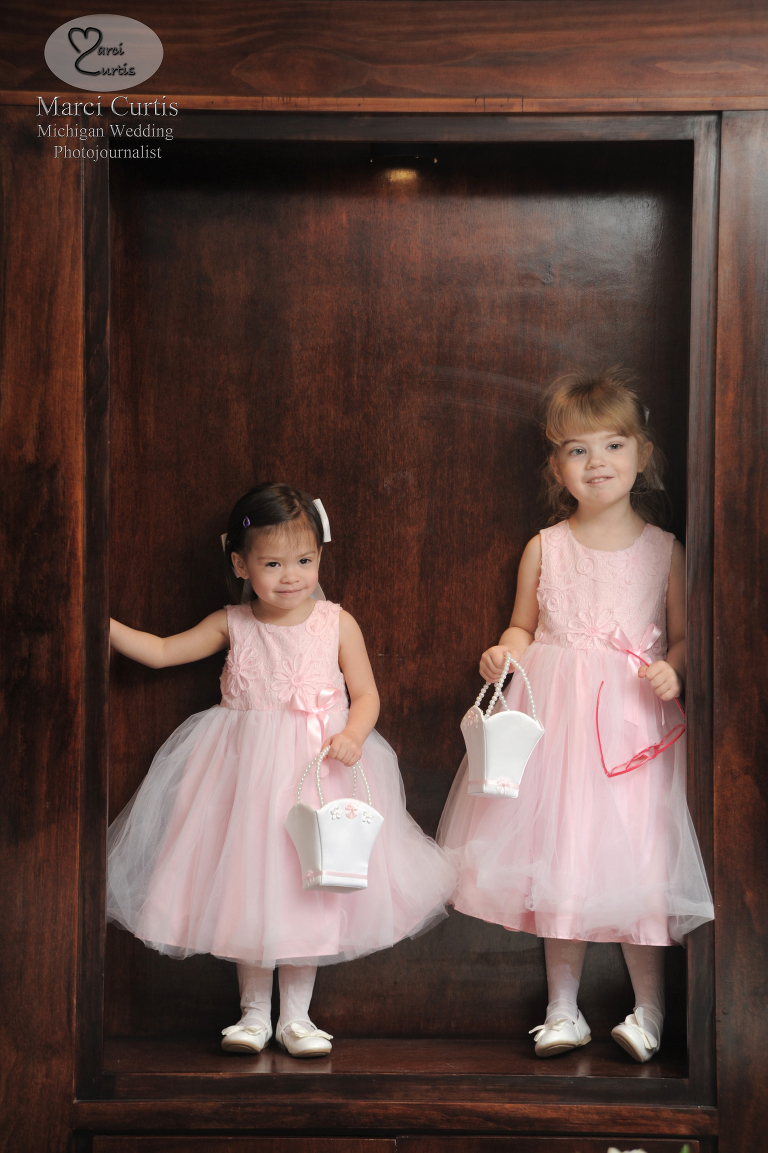 Two girls wait for a wedding to begin and wait in a bookshelf at the Iroquois Club in Bloomfield Hills Michigan.