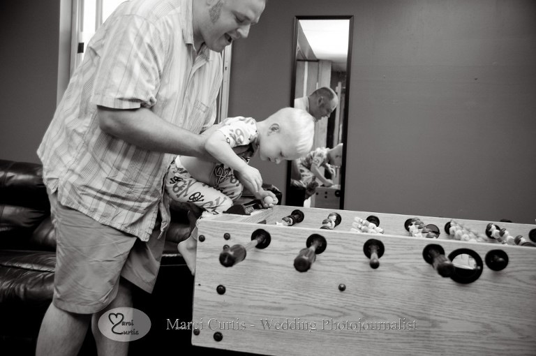 The groom plays foosball with the ring bearer before the Paw Paw Michigan wedding ceremony.