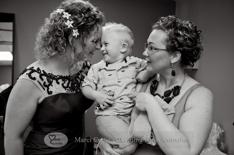 The bride gets a kiss from her bridesmaid's son shortly before the ceremony in Paw Paw, MIchigan.