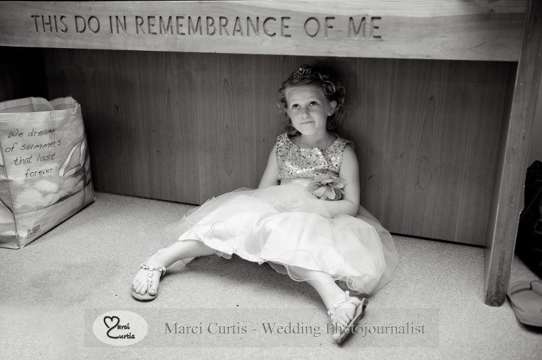 The flower girl, Adeline, rests under the altar while the bridesmaid's get ready for a wedding in Paw Paw, Michigan.