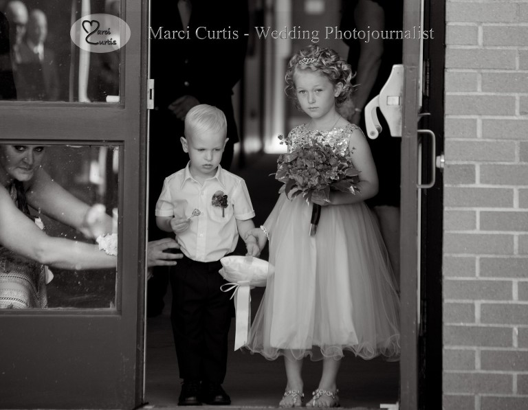 The flower girl and ring bearer are stopped from starting their entrance by the ring bearer's mom during the Paw Paw, Michigan wedding ceremony.