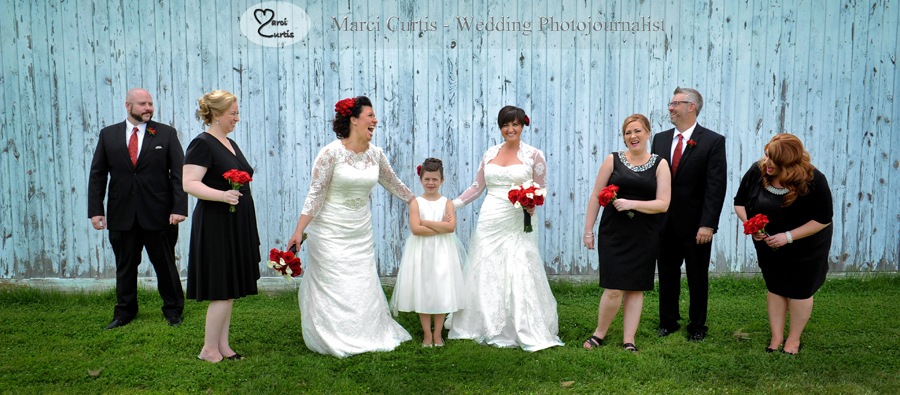Jenn and Emily pose with their daughter, and their wedding party at a barn at Greenmead in Livonia, Michigan on their long planned wedding day, June 26th, 2015. Photo by Marci Curtis - Michigan wedding Photojournalist.