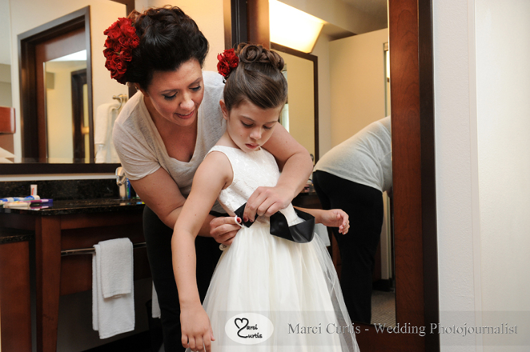 Emily helps her daughter E get into her junior bridesmaids dress on her historic June 26th, 2015 wedding day in Livonia, Michigan. Photo by Marci Curtis - Michigan Wedding Photojournalist.