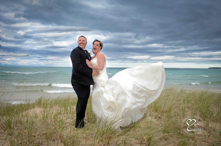 The bride's dress takes flight during her wedding day shoot in Port Austin, Michigan on the shores of Lake Huron.