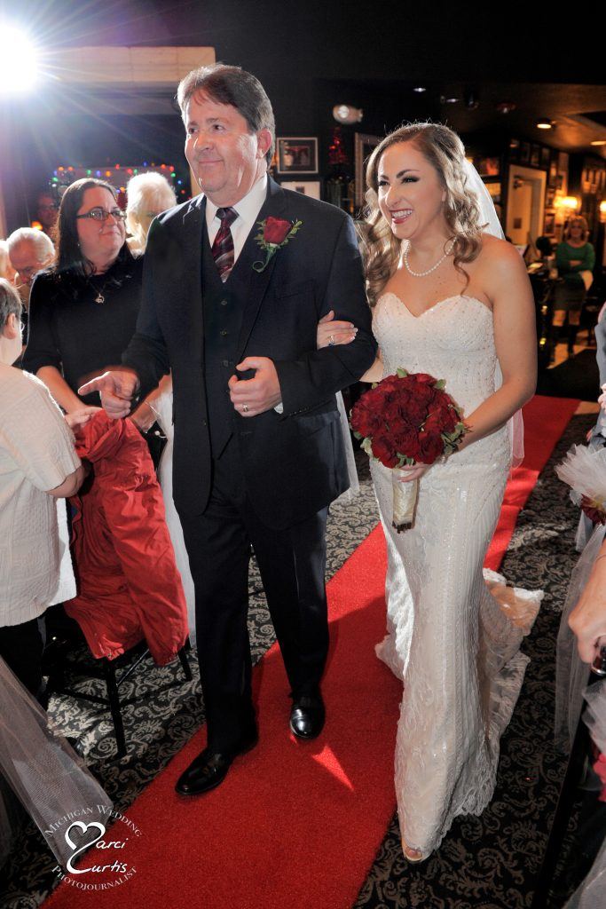 Michigan winter bride is escorted down the aisle at Steven Lelli