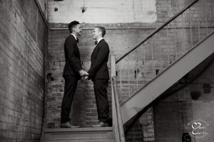 Same sex wedding couple on stairs at Detroit Michigan's Jam Handy wedding venue.