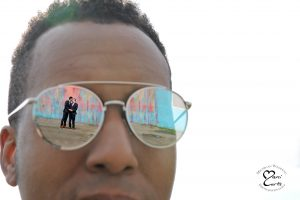 A couple is reflected in their officiant's eyes at Detroit's Bleeding Rainbow wall.