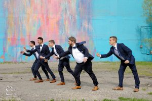 Gusty winds made standing still difficult during wedding party photos in Detroit, Michigan.