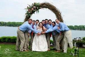 The groom and the groomsmen give the bride the heimlich maneuver as they hug the comedian during a group hug.