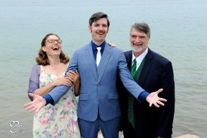 The groom obviously gets his sense of humor from his family during family photos at this lakeside wedding in metro Detroit, Michigan.