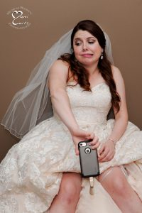 The bride cools off using a borrowed cell phone with a fan during her fun metro Detroit, Michigan wedding