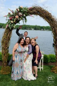 A sibling photo bombs his sister's silly photo at a wedding full of comedian's and improvisation comics in Michigan.