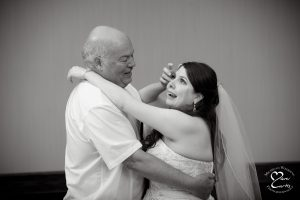 The bride wipes away tears at the White Oaks Golf Course wedding in White Lake, Michigan.