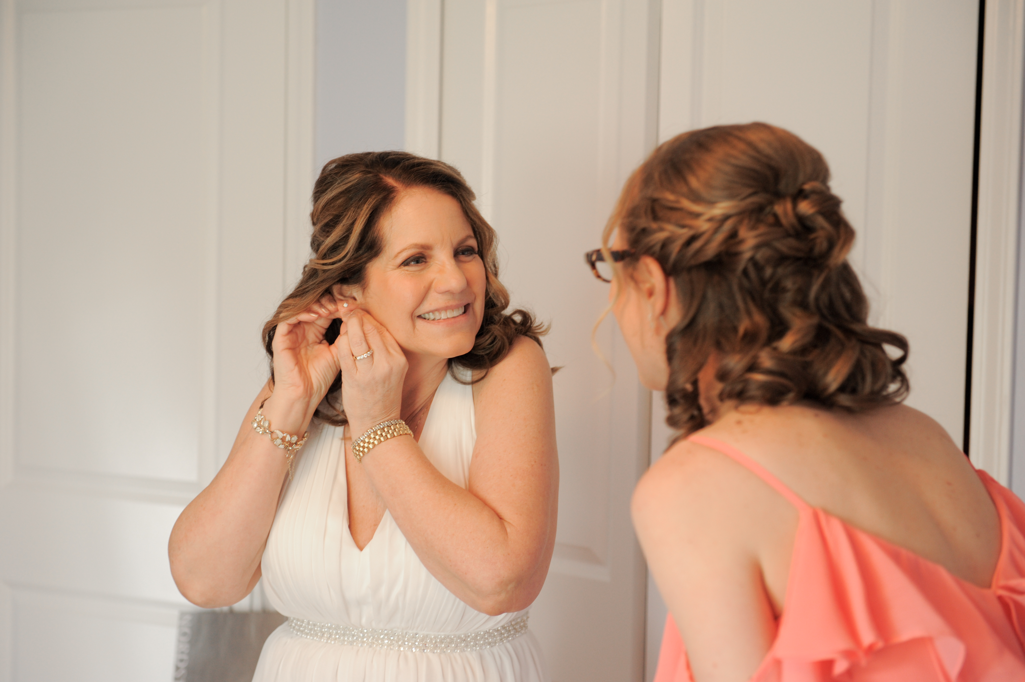 Michigan bride is helped into her dress by her new daughter in law. Photos by Marci Curtis