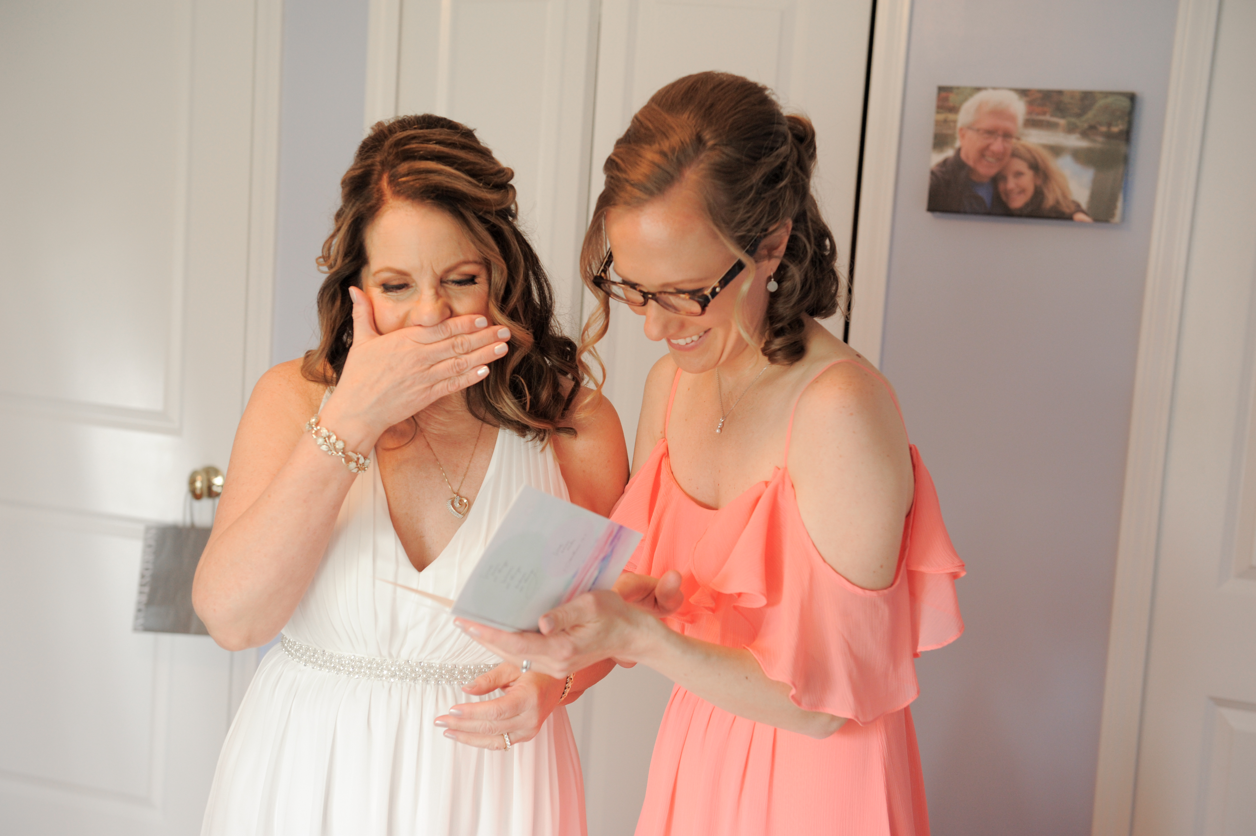 The bride and her new daughter in law giggle and cry over the note her husband to be sent her before her Detroit, Michigan wedding. Photos by Marci Curtis