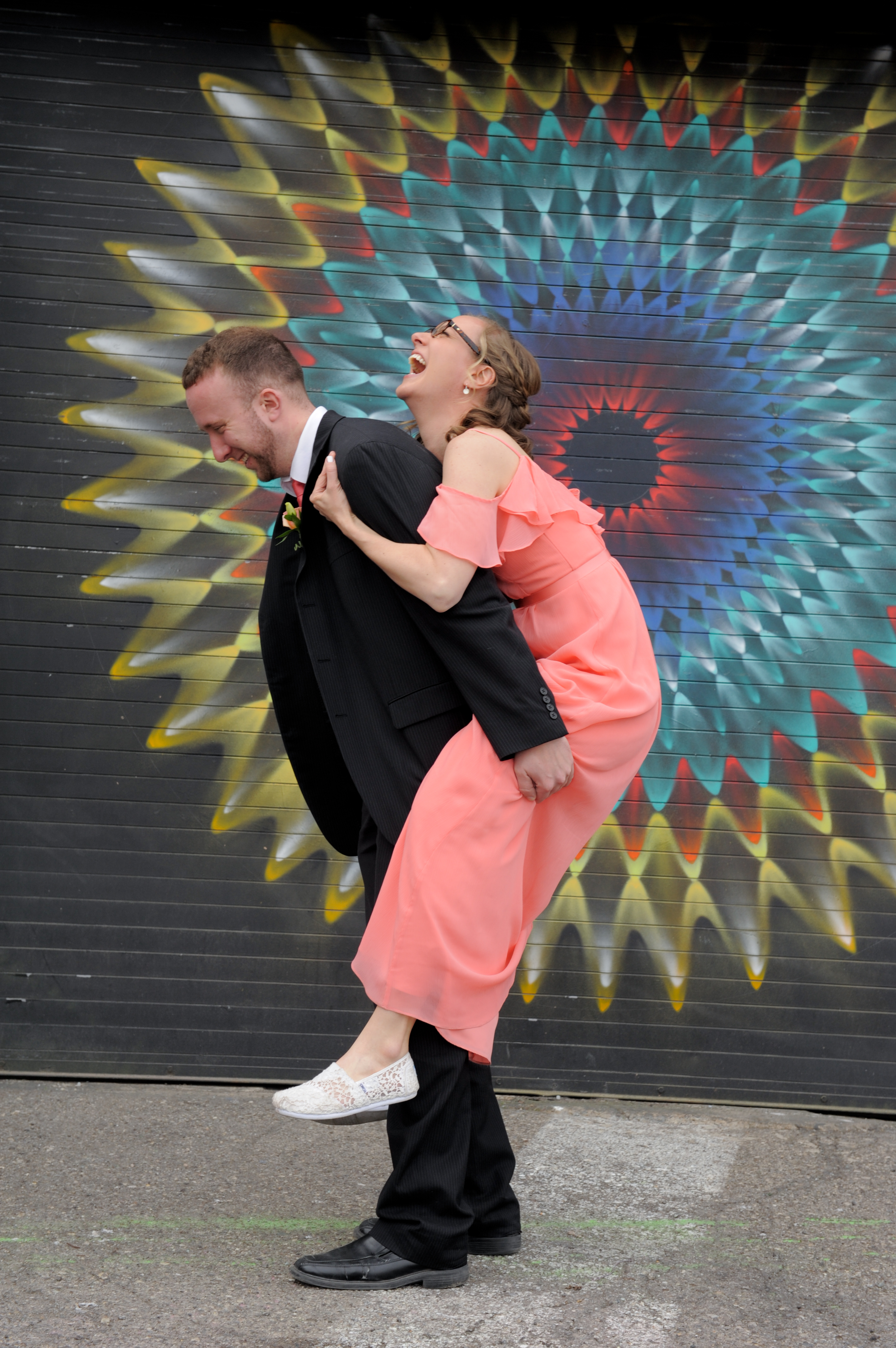 The best man reacts as his sister (and matron of honor) tries to jump on his back. Photos in Detroit's Eastern Market. Photos by Marci Curtis