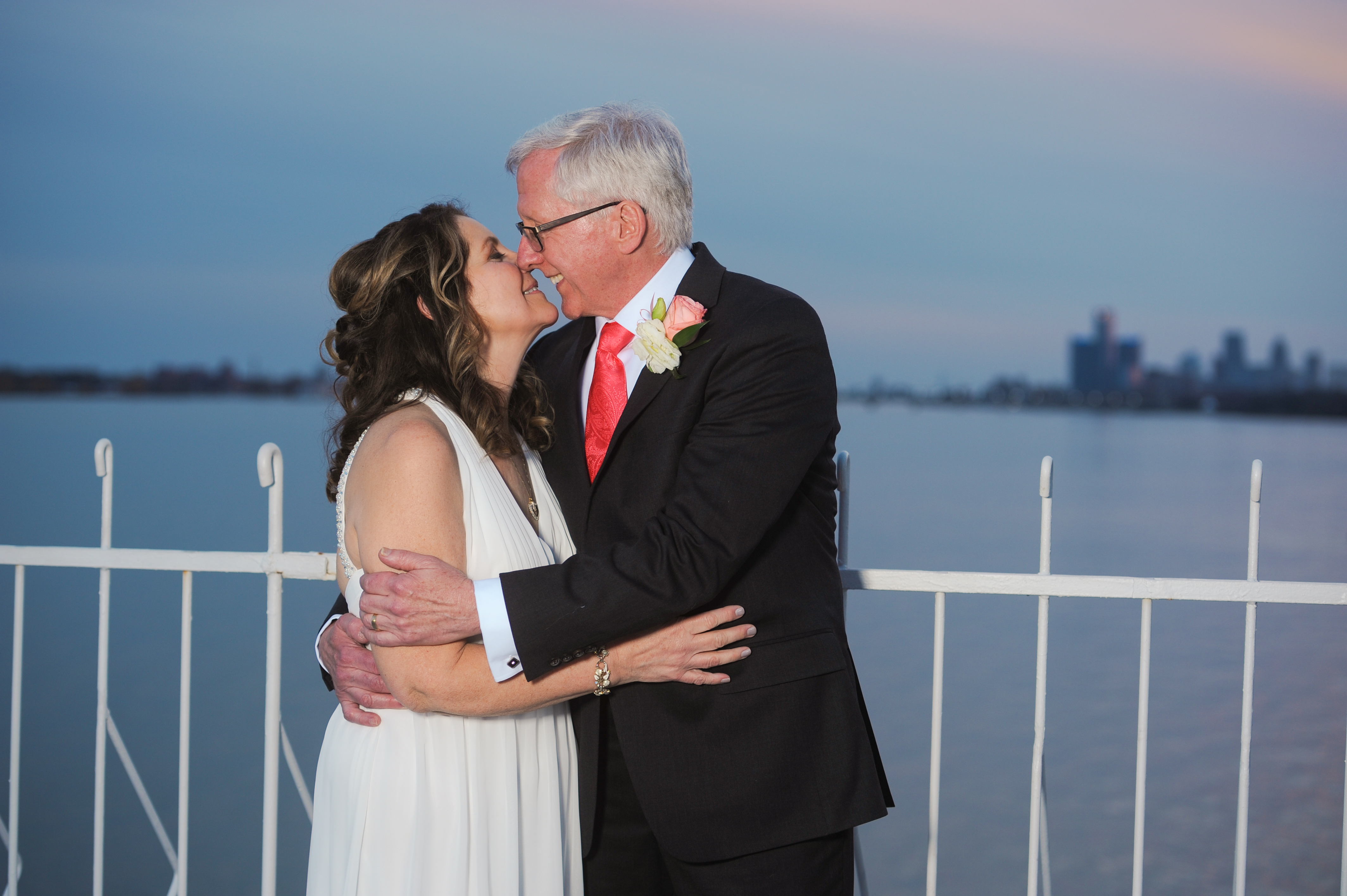 Michigan couple celebrate their second wedding on the balcony of the Roostertail wedding venue downtown Detroit. Photos by Marci Curtis