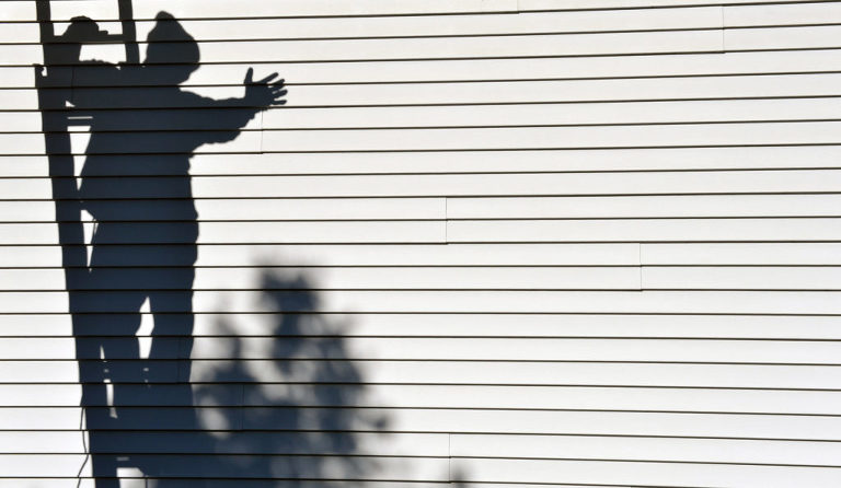 Strawberry Solar worker's shadow directs where to put a solar panel on the roof of our Michigan wedding photography business. Photo by Rodney Curtis