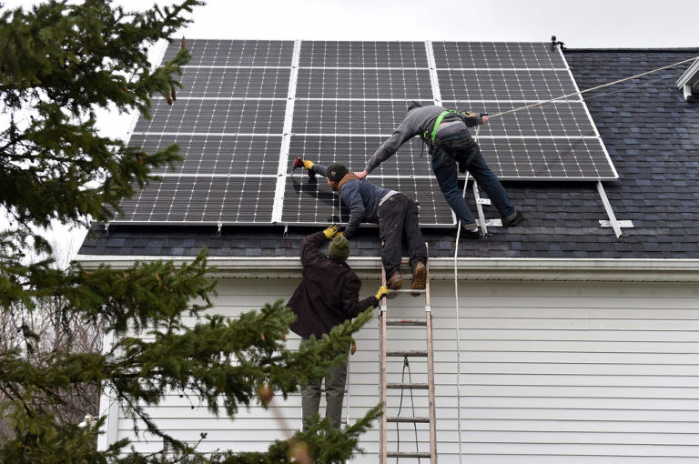 Strawberry Solar workers stretch out to secure a panel on the roof of our Michigan wedding photography business. Photo by Rodney Curtis