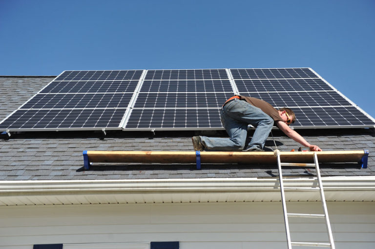 Strawberry Solar worker installs a panel on the roof of our Michigan wedding photography business. Photo by Rodney Curtis