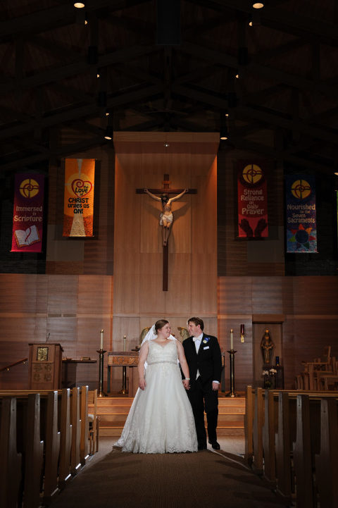 The bride and groom walk down the aisle after their wedding at the St. Louise de Marillac church in Warren, Michigan. Photo by Marci Curtis