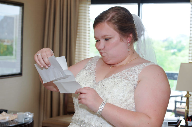 Bride reads a sweet note from her groom and makes this face to avoid cryting at the Townsend hotel in Birmingham, Michigan. Photo by Marci Curtis