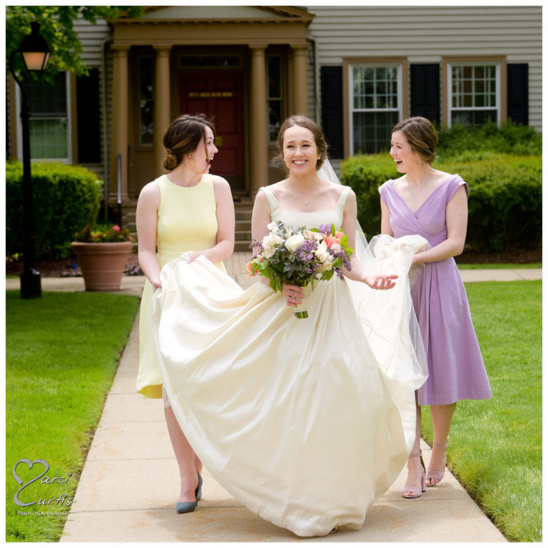 The bride's sisters laugh about something while wrangling her dress at the Dearborn Inn in Dearborn, Michigan.
