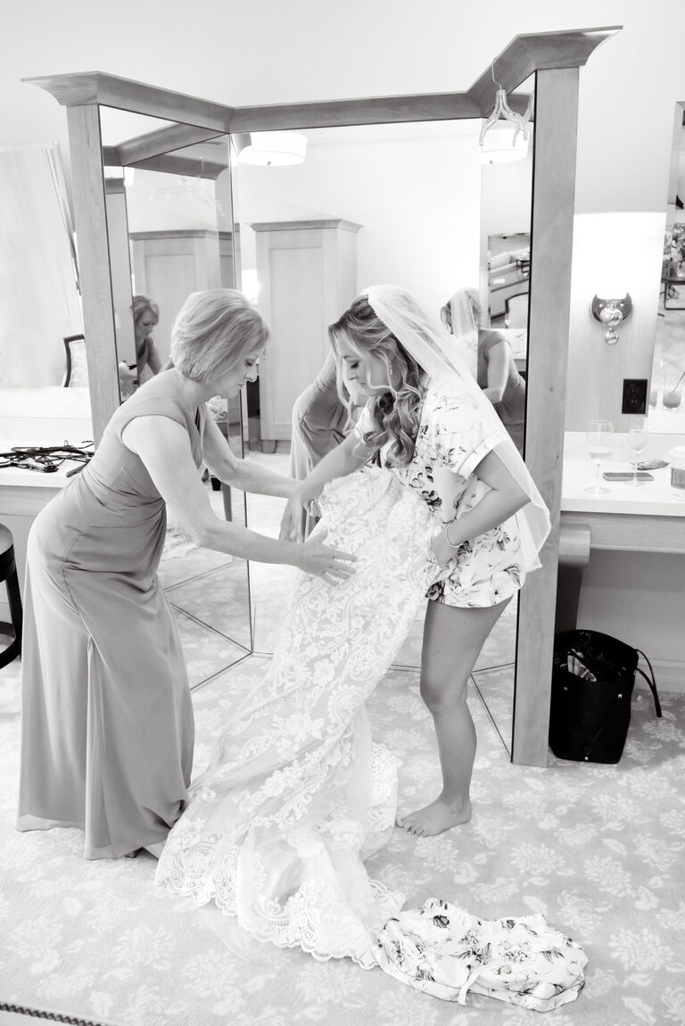 The bride's mother helps her into her dress in the bridal suite at Shepherd's Hollow Golf Club.