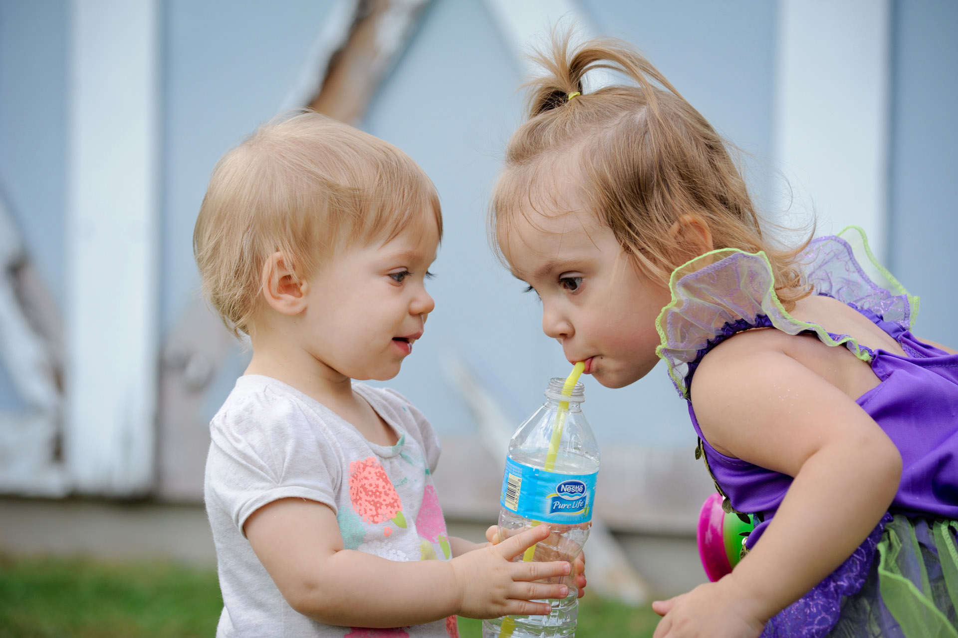 Best Detroit children photographer takes candid children photos with the children throughout the photography session so I can get little moments like this sister offering her big sister a drink from her water bottle in metro Detroit, Michigan.