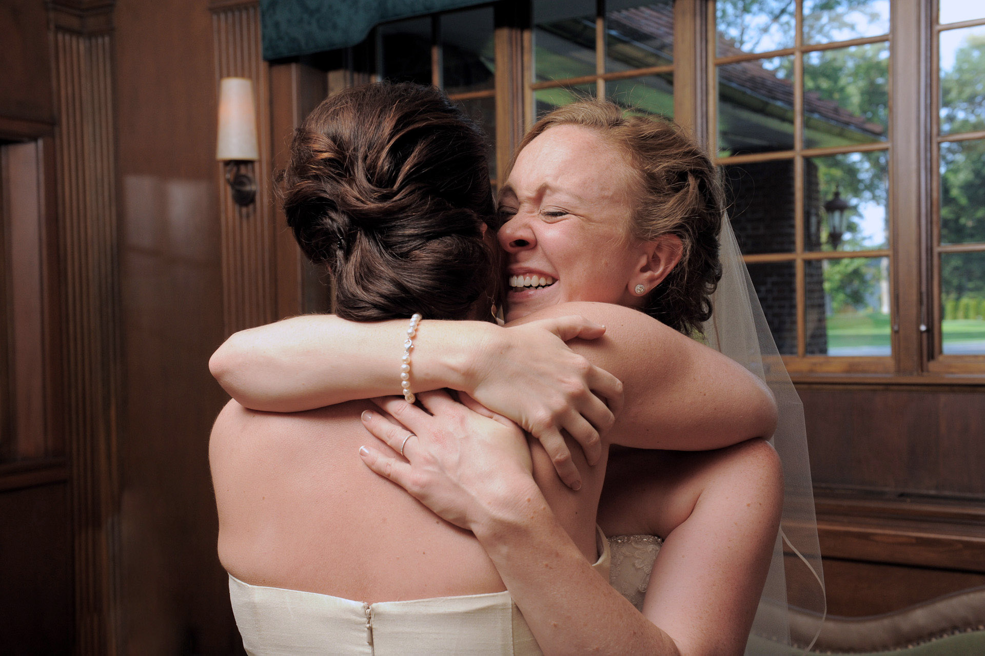 Detroit Golf Club wedding photographer's photo of the bride sharing a cry with one of her bridesmaids after her wedding ceremony at the Detroit Golf Club.