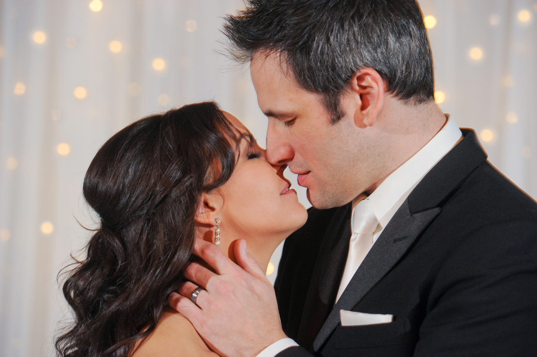 An artistic couple at the Royal Park Hotel in Rochester kiss during their intimate ceremony in Rochester, Michigan.
