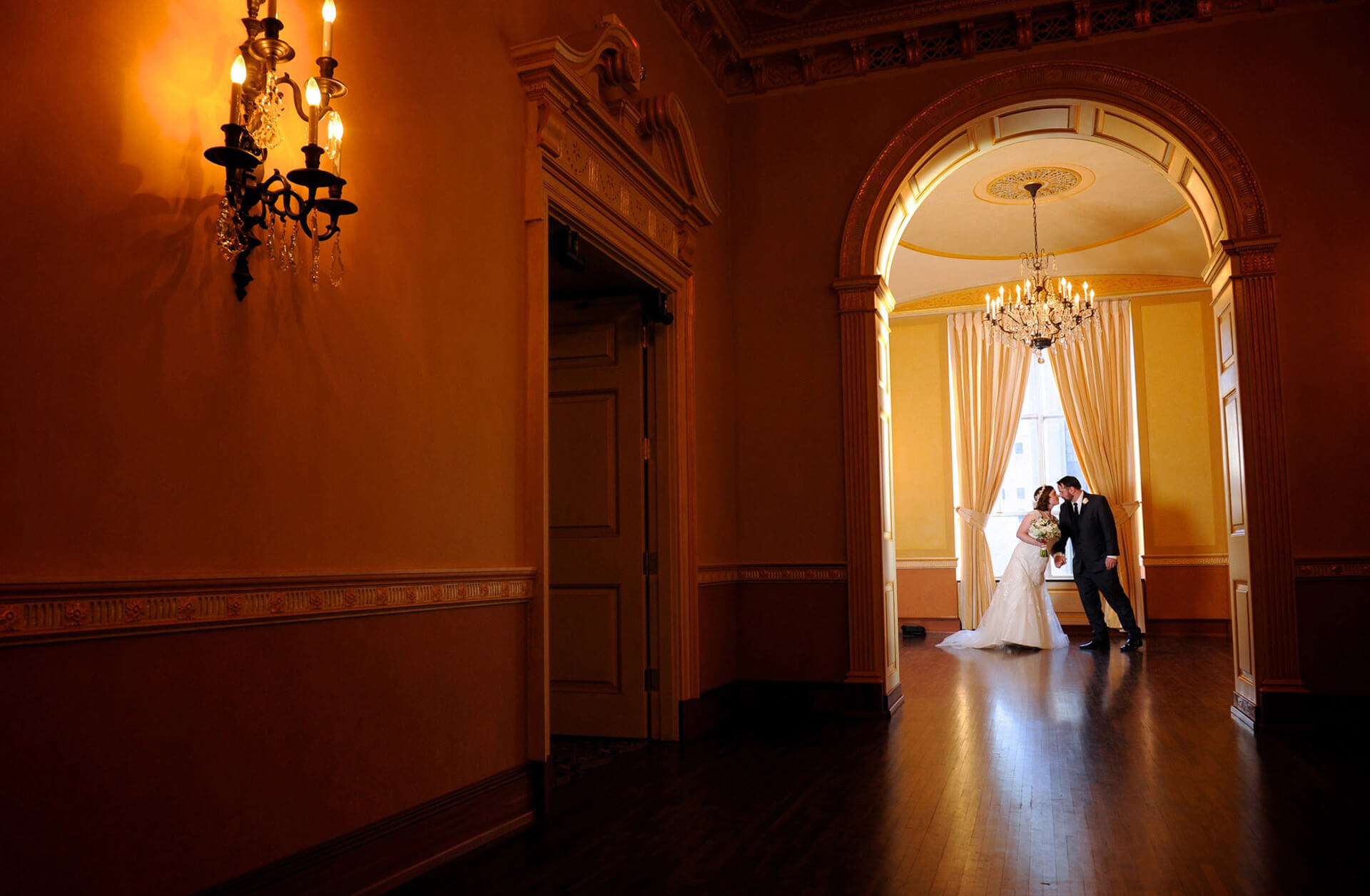 The bride and groom share a kiss at Detroit's Colony Club wedding reception venue.
