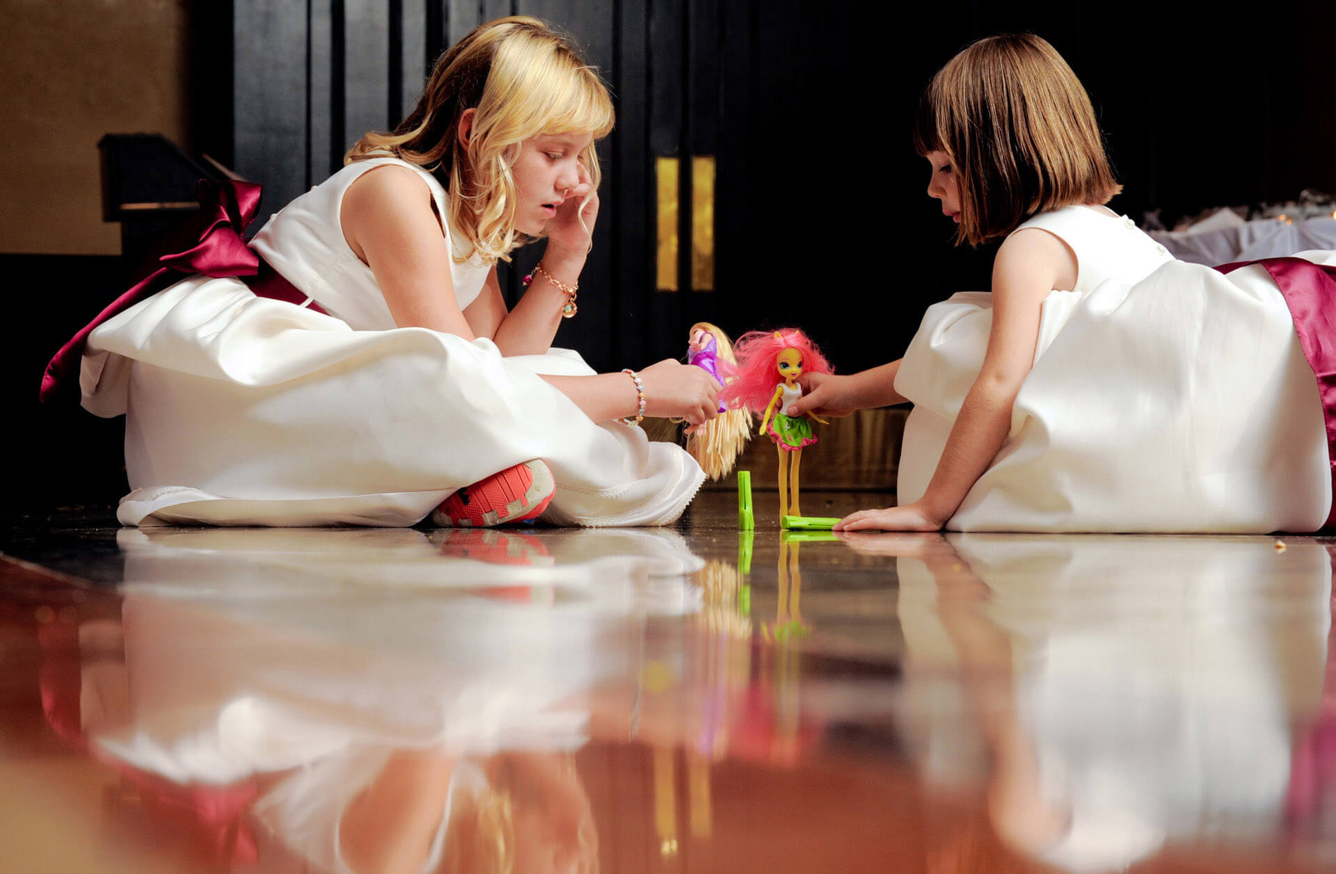 Two flower girls amuse themselves at their Rochester, Michigan wedding reception flaying with barbies on the dance floor before the wedding reception begins at the Royal Park Hotel.