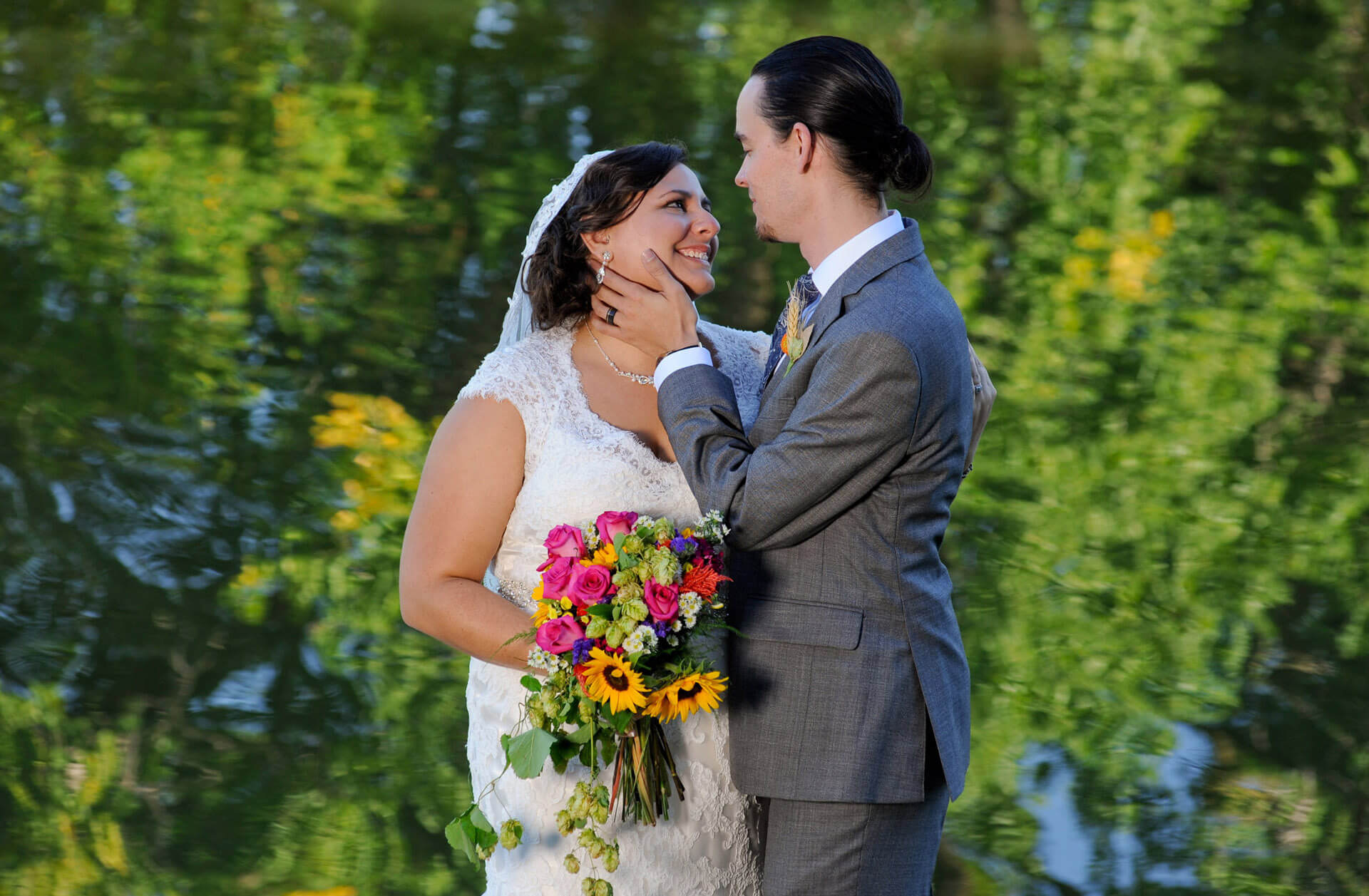 The bride and groom take a quite moment in Frankenmuth, Michigan along the river where trees are reflected in the water.