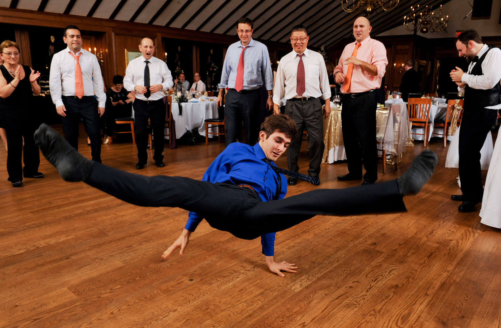 A wedding guests starts to break dance at a King's Court Castle wedding at Canterbury Village in Lake Orion, Michigan wedding taking place at the Canterbury Village during a winter wedding in Michigan.