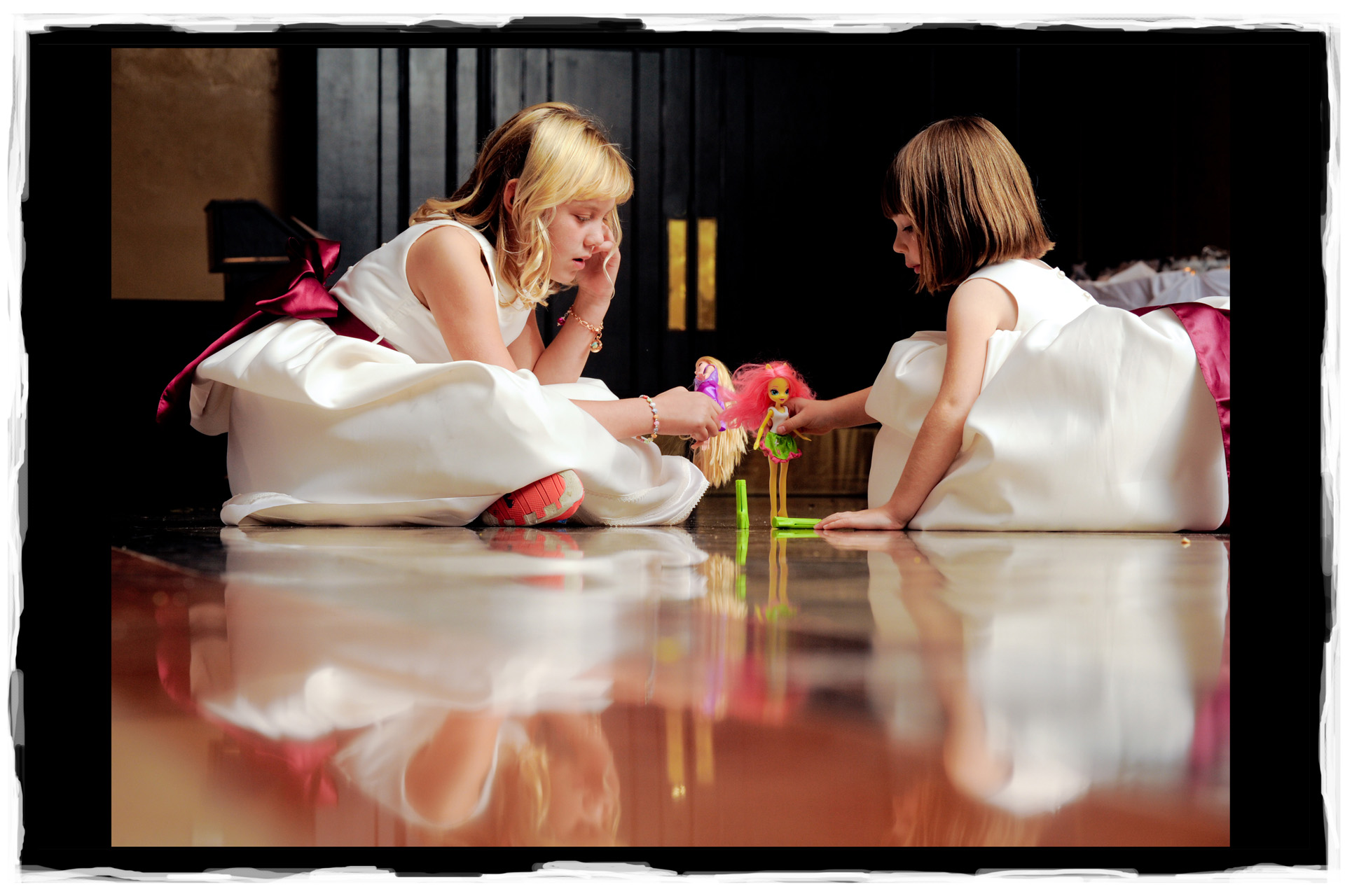 Two flower girls decide to play Barbies during their Oakland County, Michigan wedding reception.
