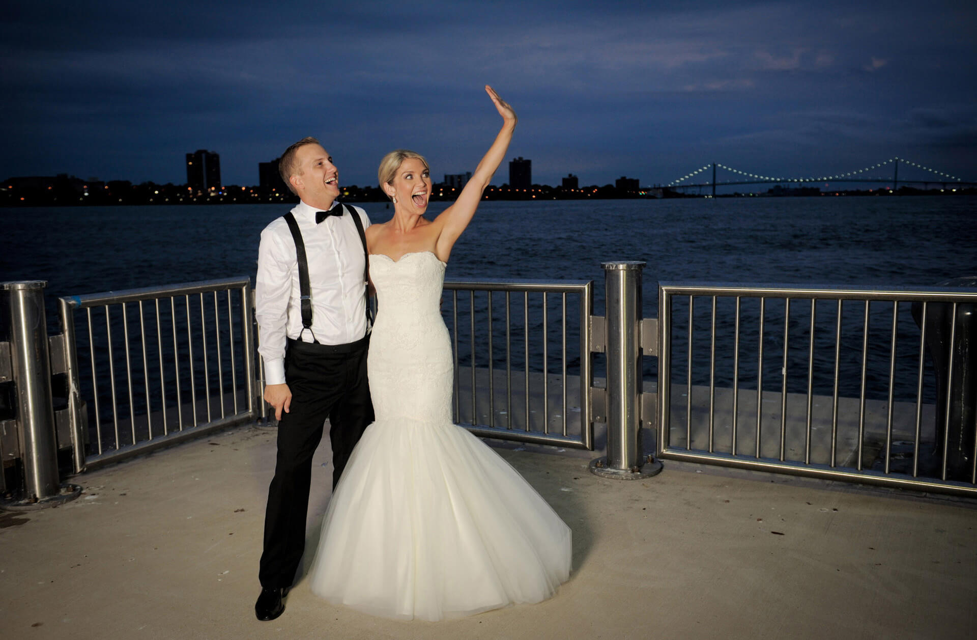 The bride and groom wave to their guests from Detroit, Michigan's waterfront vantage point during their Waterview Loft wedding reception.