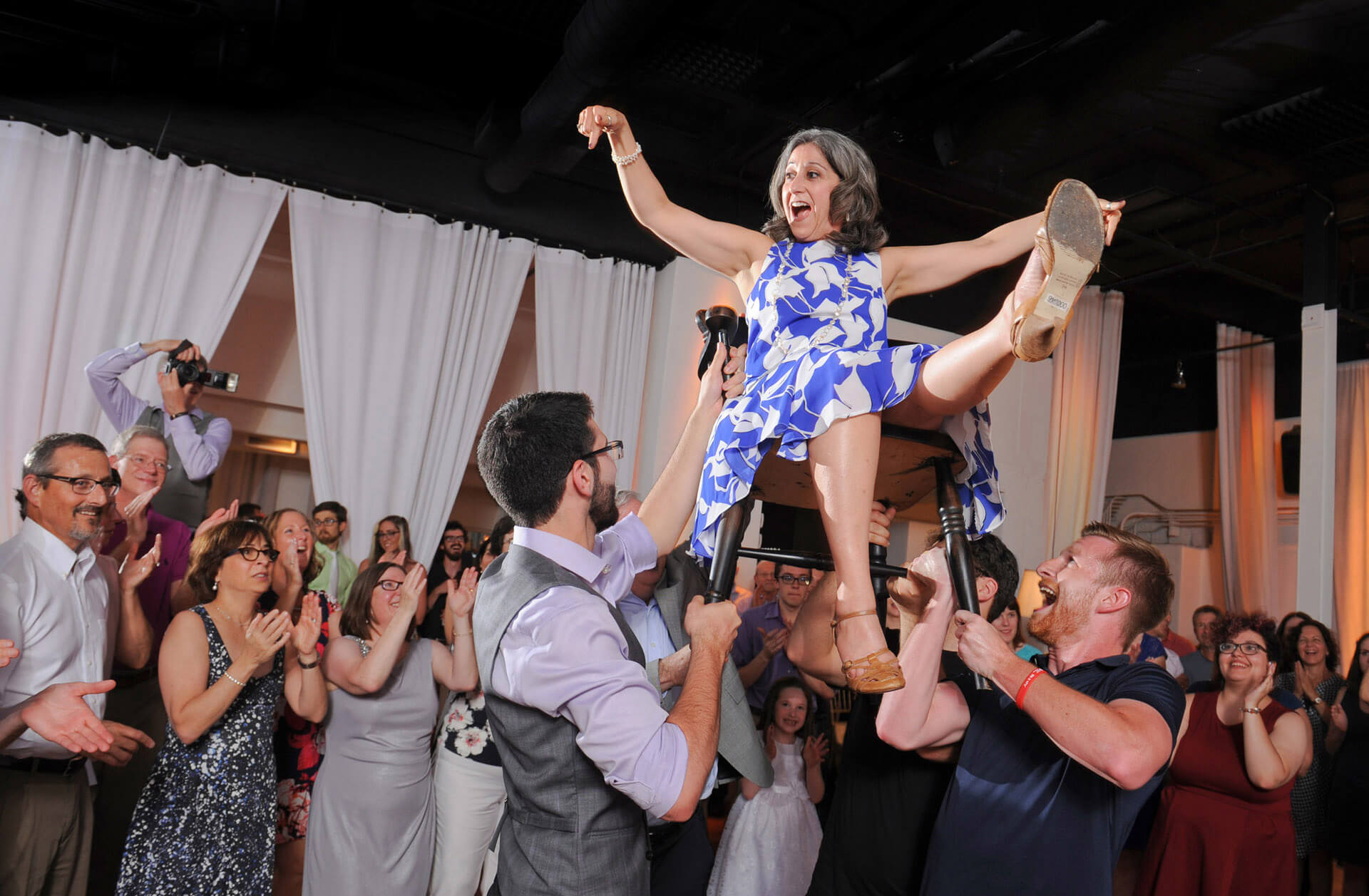 The mother of the groom indicates that she'd like to be put down immediately during the Hora at a Jewish wedding in Ferndale, Michigan.