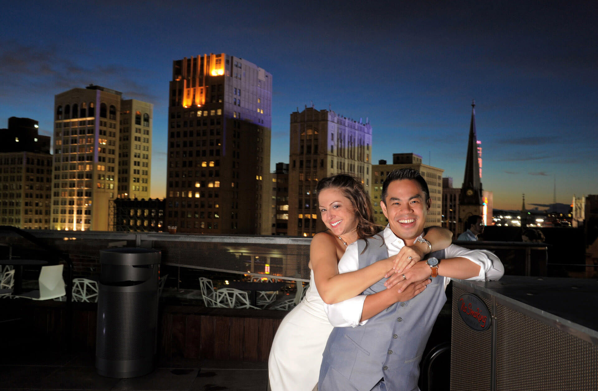 A bride and groom snuggle just after sunset on their rooftop wedding reception location in Downtown Detroit, Michigan.