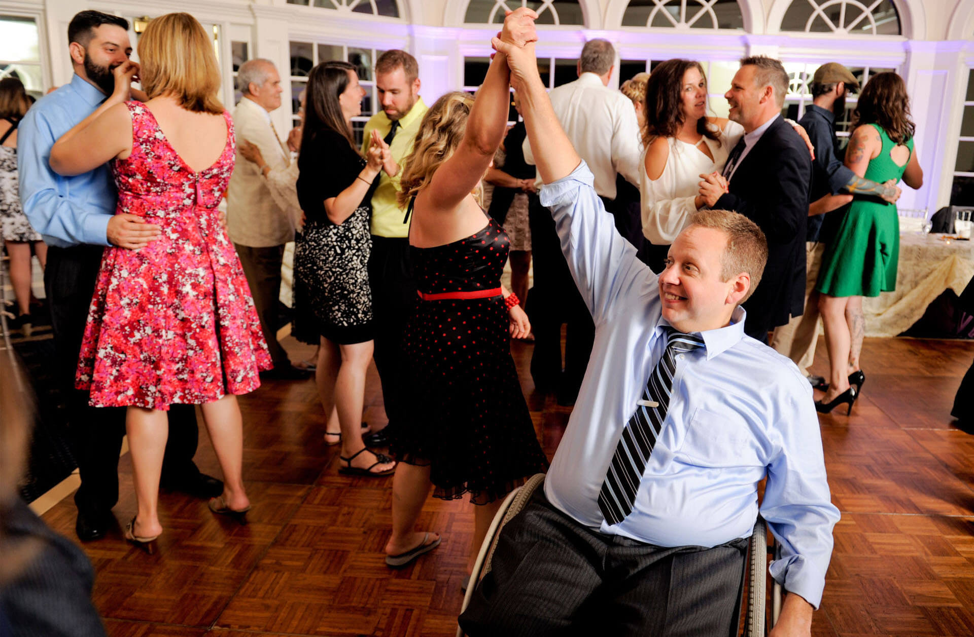 A couple dance on the tight dance floor at Cherry Creek in Shelby Charter Township, Michigan and manage to dance at the wedding reception easily navigating the guest's wheelchair.