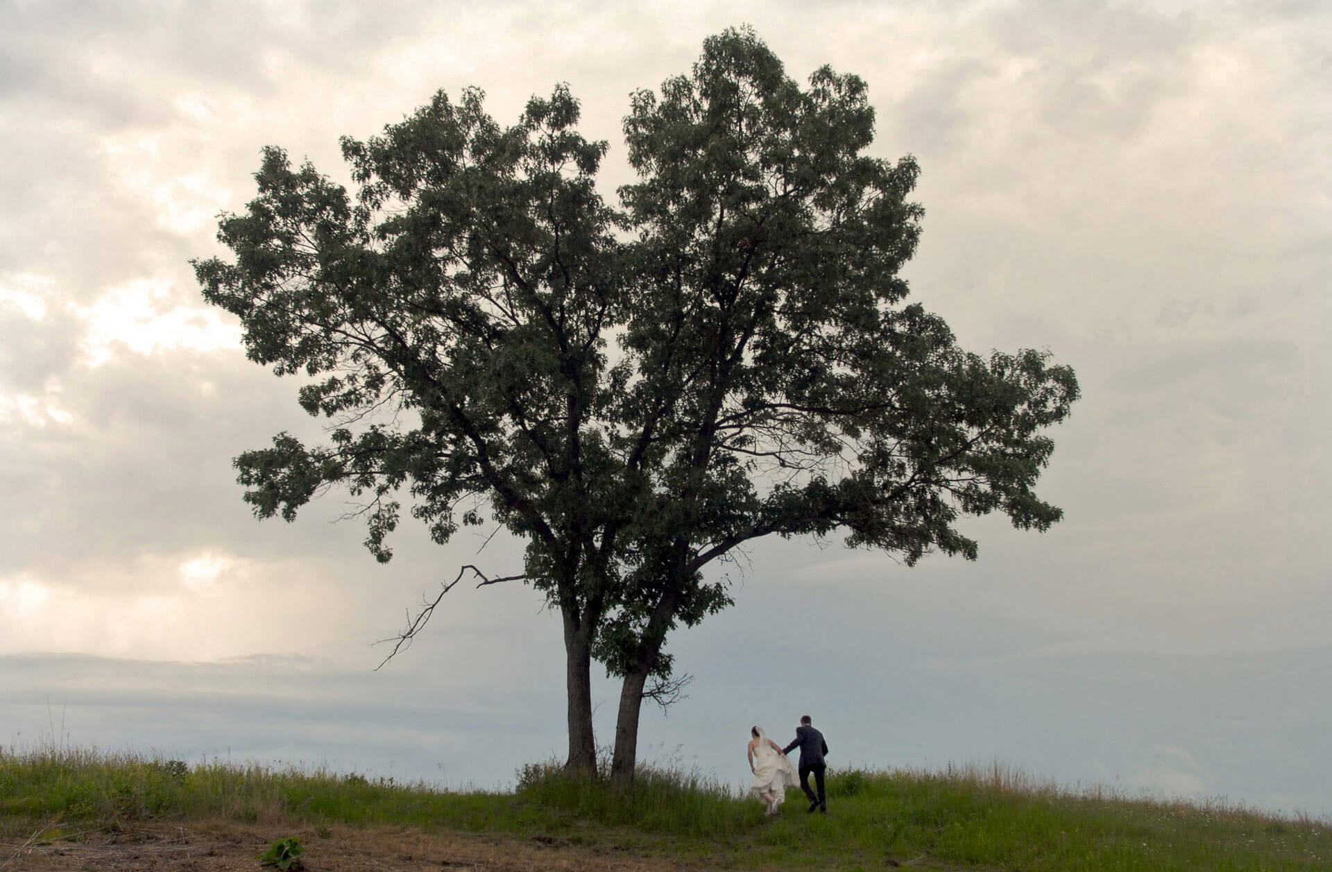 A Michigan couple head up the hill at Indian Springs wedding venue during a spring storm for a dramatic wedding photo.