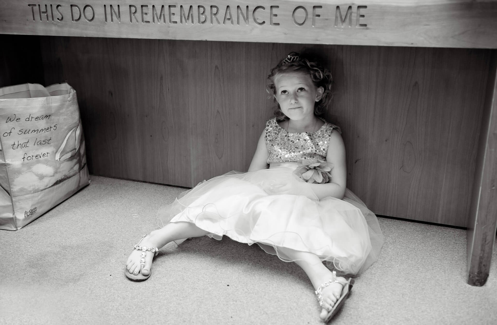 A flower girl hides under the altar while the Michigan bride gets ready during this Washtenaw County Michigan wedding.